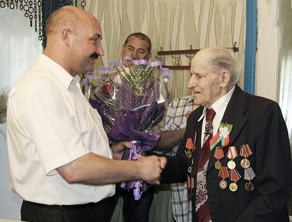 Председатель райисполкома Сергей ЯКОВЛЕВ поздравляет ветерана с юбилеем. Фото Раисы БОРОВОЙ.