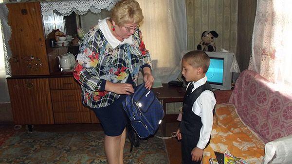 Председатель районного Совета депутатов Валентина ГАНКОВИЧ вручает портфель со школьными принадлежностями Николаю ПАНИЧКОВУ.