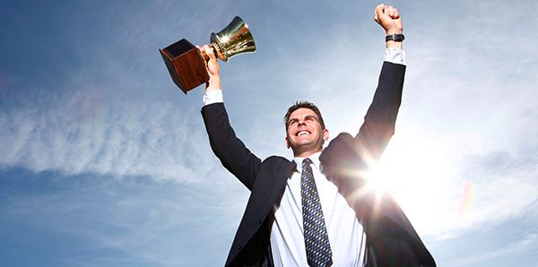 Businessman celebrating with trophy in hand